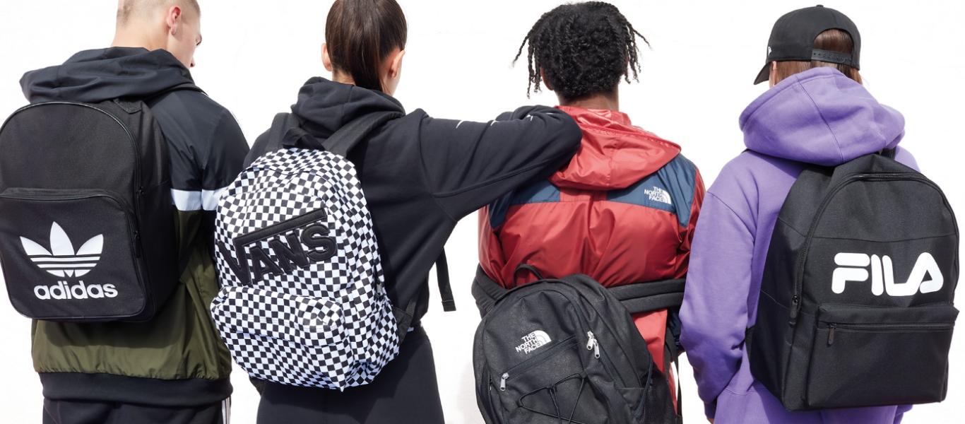 På billedet ses 4 personer. Alle står med ryggen til. På ryggen har de hver en rygsæk. Første rygsæk fra venstre er af mærket adidas. Tasken er sort med et stort adidas Trifoil logo på fronten. Anden rygsæk fra venstre er af mærket Vans. Tasken er sort og hvid, mønstret som et skakbræt, med et stort sort broderet VANS logo på fronten. Tredje taske fra venstre er af mærket The North Face. Tasken hænger længere nede på ryggen and de andre tasker på billedet og viser at personen har en jakke på af samme mærke. Tasken er sort med et lille The North Face ogo på toppen. Jakken er primært rød men med blå skuldre. På højre skulder ses det samme lille The North Face logo. Sidate taske på billedet er af mærket FILA. Tasken er sort med et stort FILA mærke i hvid på fronten.