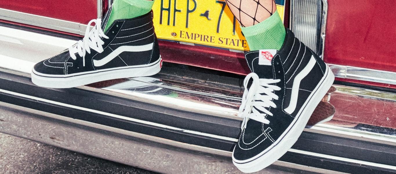 på billedet ses bagenden af en bil hvor et par Vans Sk8-Hi i sorte og hvide er placeret på kofangeren.