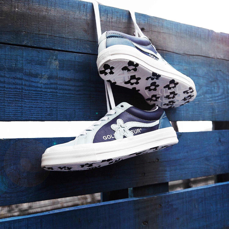 På billedet ses et par af de nye Golf e Fleur fra Converse. Sneakeren er designet af rapperen og modeikonet Tyler The Creator. Sneakerene ses hænge på et hegn. Modelen er mørkeblå med lyseblå og hvide detaljer.